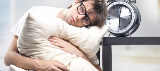 Sad man holding pillow and the clock